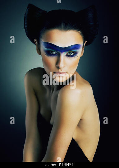 Art portrait of spectacular young bare girl with theatrical makeup on her face studio shot - series of photos - Stock Image