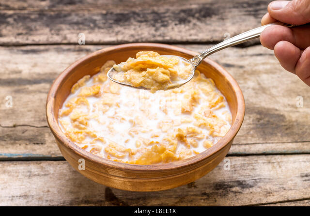 Clay bowl of corn flakes. Healthy eating background - Stock Image