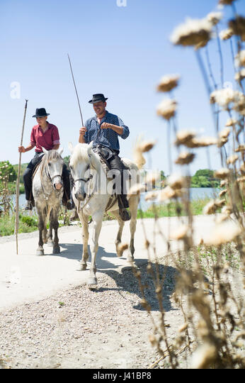 Gardians and their Camargue horse in front of their Manade, near Aigues-Mortes, Camargue, Gard, Languedoc-Roussillon, - Stock Image