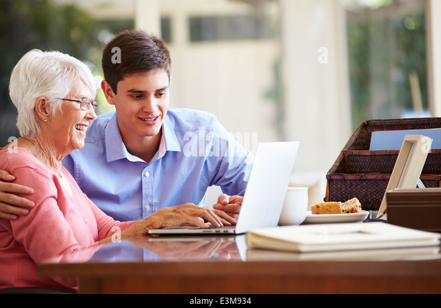 Teenage Grandson Helping Grandmother With Laptop - Stock-Bilder