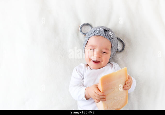 Baby boy in mouse hat lying on blanket with cheese - Stock Image