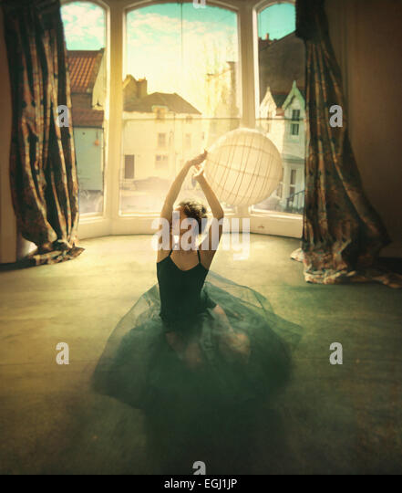 young female dancer siting on the floor - Stock Image