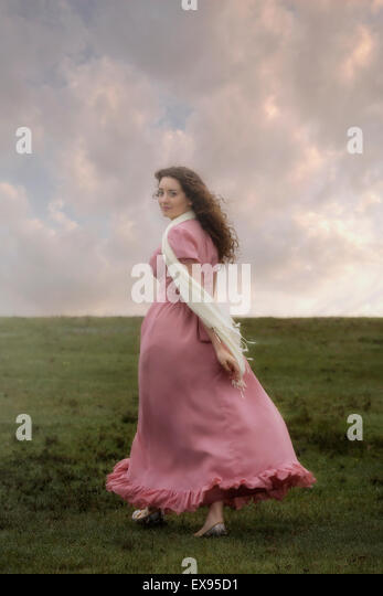 a woman in a pink dress is walking up a hill - Stock Image