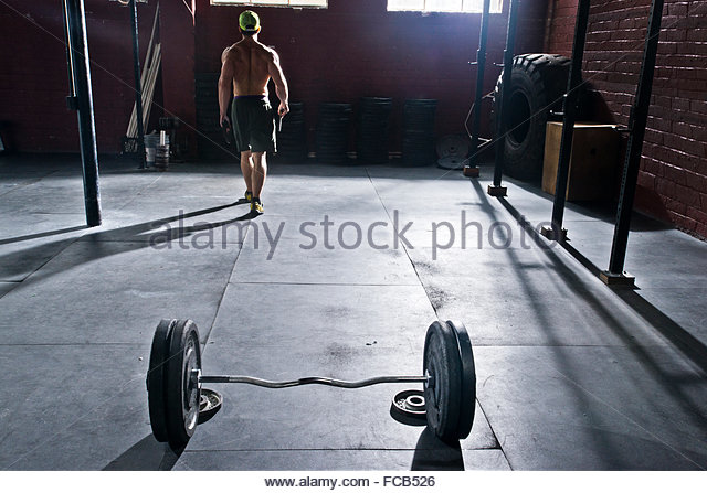A crossfit athlete racks his weights after working out. - Stock Image