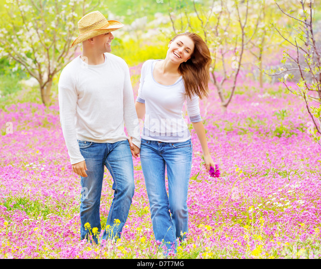 Beautiful happy couple enjoying spring nature, laughing and having fun outdoors, walking on purple floral glade, - Stock Image