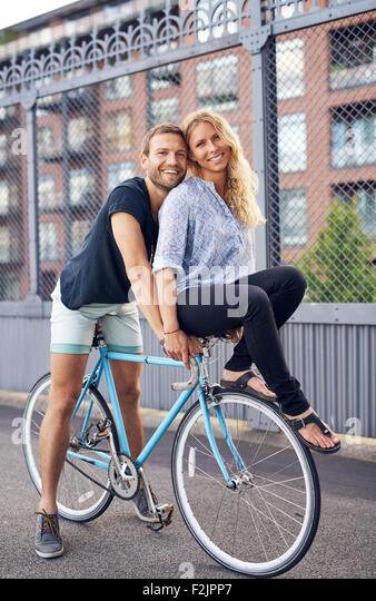 Loving couple riding bikes, woman on handlebar - Stock-Bilder