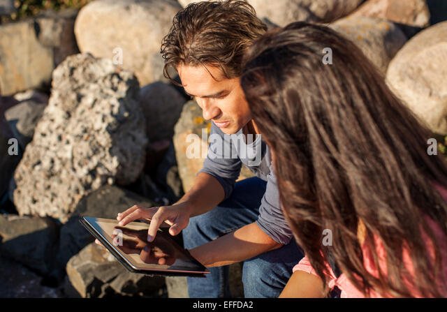 Young couple using digital tablet on rocks - Stock Image