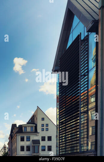 Latvia, Riga. Triangles on the roofs of old and modern houses with reflection of the Church of St. Peter in the - Stock Image