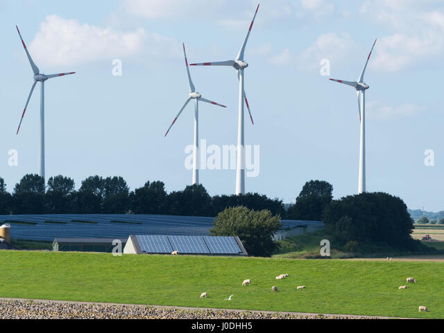 Wind Turbines and solar panels in front of blue sky - Stock Image
