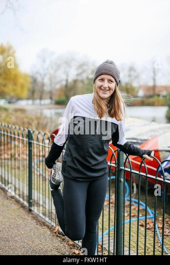 Teenage girl doing preparation warm up in park - Stock Image