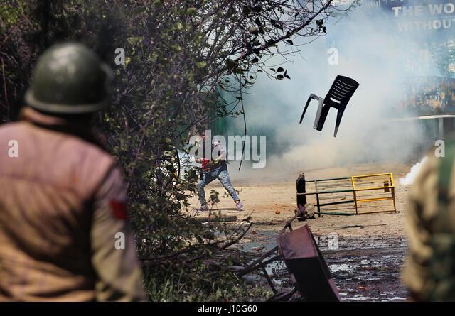 Srinagar, Kashmir. 17th Apr, 2017. A Kashmiri student throws a chair at Indian police during a protest outside a - Stock-Bilder