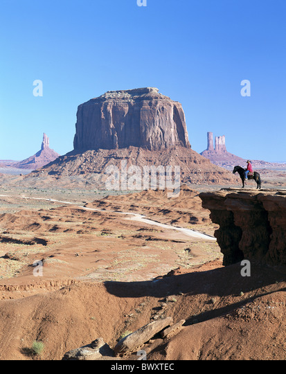 America Arizona cowboy rocky cliff scenery monument Valley horse stand USA America North America - Stock Image