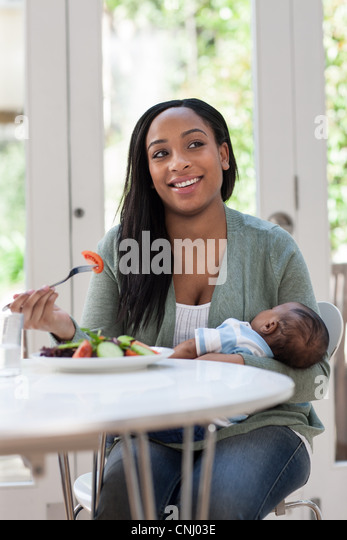 Mother holding baby son and having lunch - Stock Image