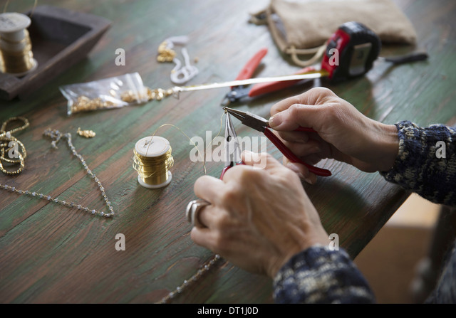 A tabletop with jewellery making equipment Hands twisting wire on a necklace - Stock Image