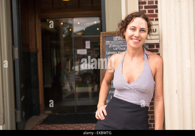 Portrait of female shop keeper in doorway of small store - Stock Image