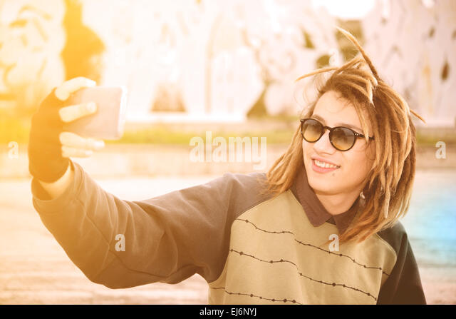 portrait of young guy outdoor with rasta hair smiling with smart phone in a lifestyle concept with a warm filter - Stock-Bilder