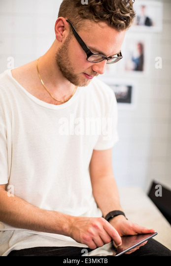 Young businessman using tablet computer in new office - Stock Image