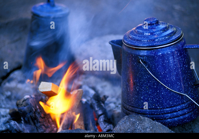 Coffee pots heating up on outdoor campfire, Middle fork of the Salmon River, Idaho, USA - Stock Image