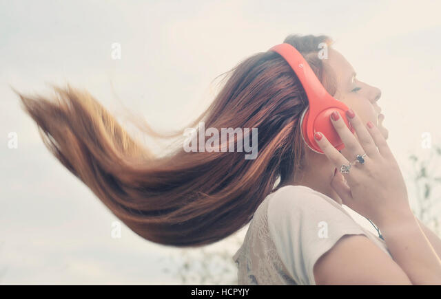 Girl is listen to the music on headphones - Stock Image