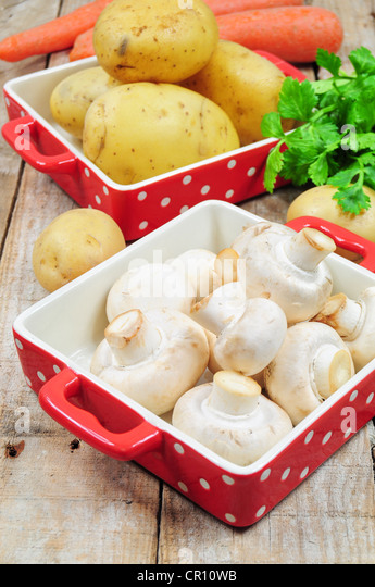 Raw mushrooms and potatoes in red trays - Stock Image