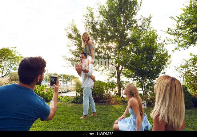 Young man photographing shoulder carrying friends in park - Stock-Bilder