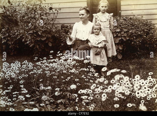 Woman and daughters posing next to flowers during the late 1800s or early 1900s mother motherhood family wooden - Stock-Bilder