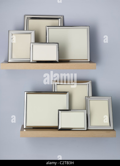 empty picture frames on shelves - Stock Image