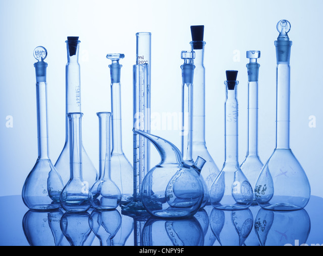 Research Lab assorted Glassware Equipment on blue background - Stock Image