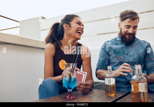 Couple sitting by a table partying and playing cards. Happy young man and woman playing cards during a party. - Stock Image