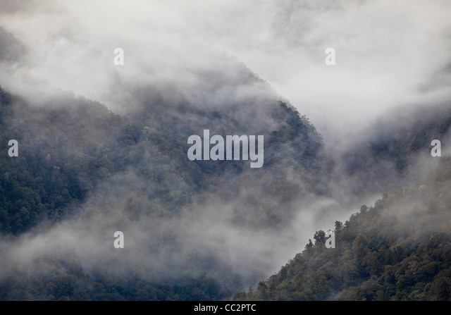 Mist blankets the mountains in Haast Pass, Canterbury, New Zealand - Stock Image
