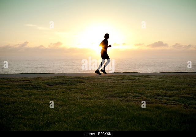 A silhouette of a jogger running alone with sun on horizon - Stock-Bilder