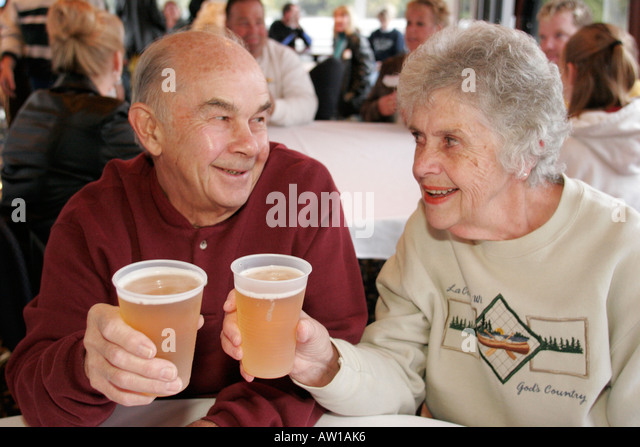 Wisconsin La Crosse Mississippi River Island Girl Yacht Cruise tour boat senior couple drink beer - Stock Image