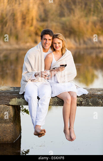 romantic couple sitting on pier and drinking wine at sunset - Stock Image