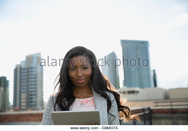 Portrait confident businesswoman using digital tablet urban rooftop - Stock-Bilder