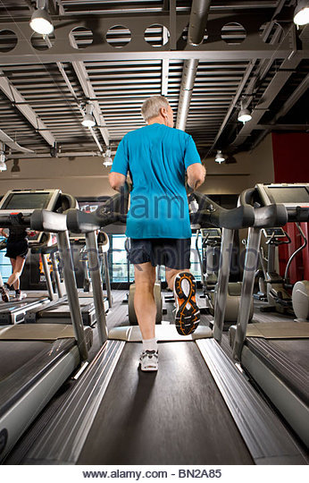 Man running on treadmill in health club - Stock Image