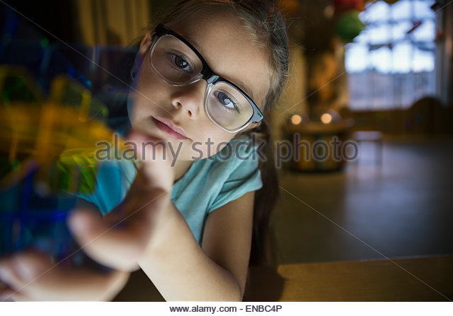 Curious girl holding geometric shape in science center - Stock Image