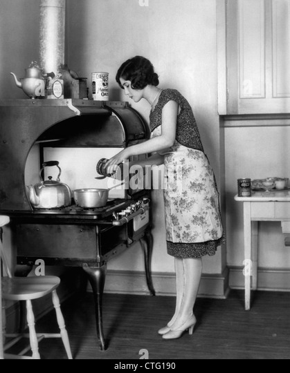 1920s HOUSEWIFE AT STOVE COOKING - Stock Image