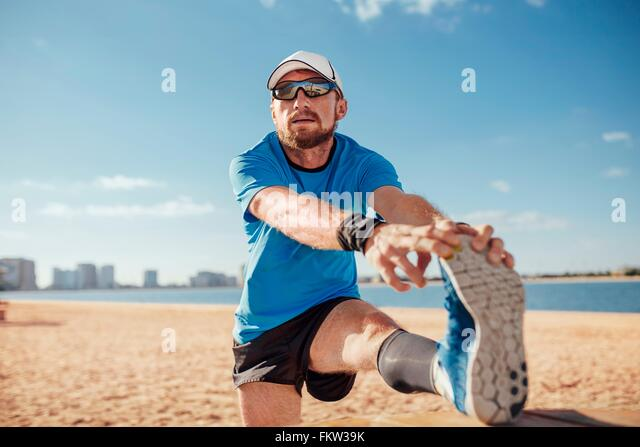 Mid adult man on beach leg raised touching toes stretching foot, Dubai, United Arab Emirates - Stock Image