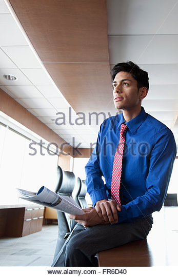 businessman in bright, urban office - Stock Image