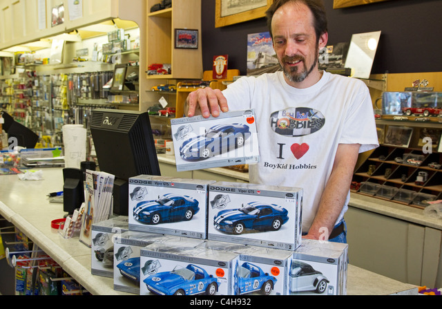 Hobby store clerk stacking model car boxes on store counter - Stock Image