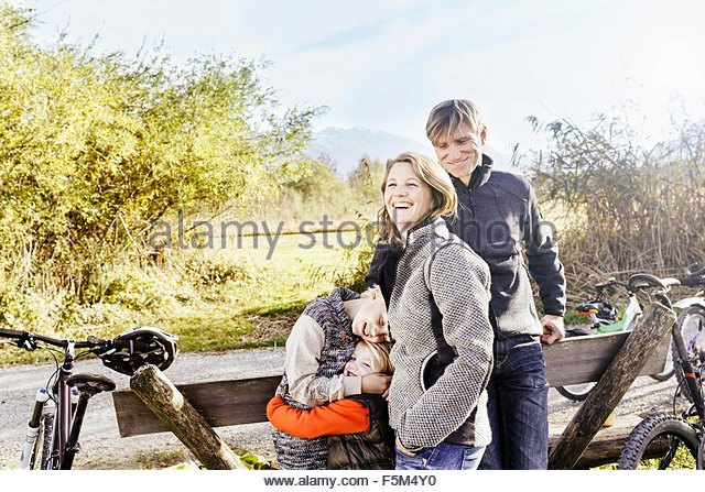Family with bicycles by roadside hugging and smiling - Stock Image