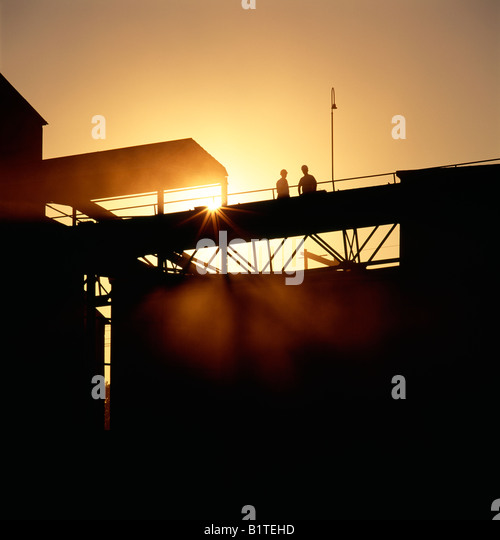 Workers silhouetted against the sunrise at a cement plant. - Stock Image