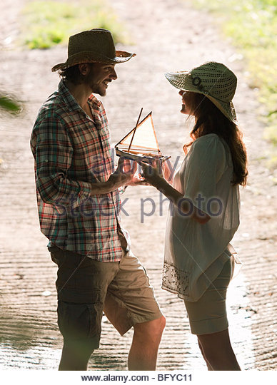 Man and woman with model boat in sun - Stock Image