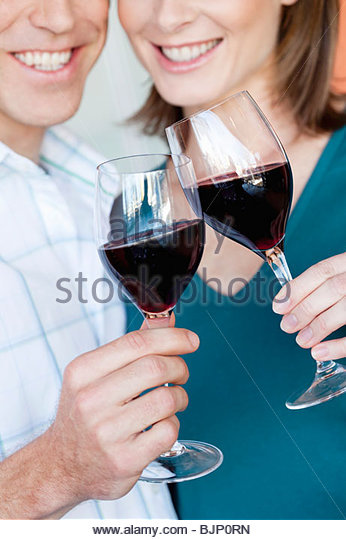 Smiling couple clinking glasses of red wine - Stock Image