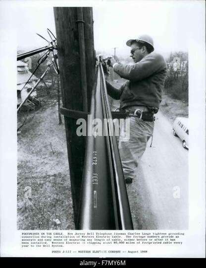 1978 - Footprints On The Cable. New Jersey Bell Telephone lineman Charles Lange tightens grounding connection during - Stock Image