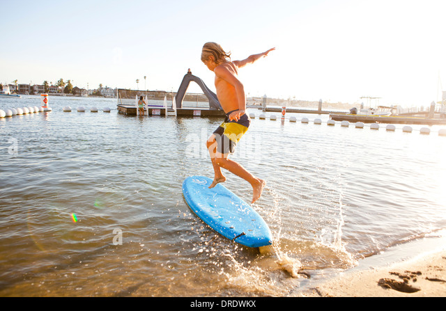 Boy surfing at the beach - Stock Image