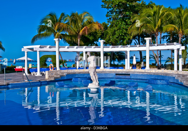 Negril JamaicaSwimming pool with bright reflections and classical statue at Hotel Riu Palace Tropical Bay all-inclusive - Stock Image