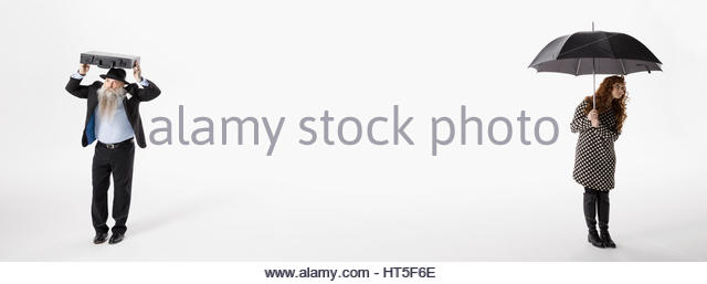 Businessman covering head with briefcase across from businesswoman using umbrella against white background - Stock-Bilder