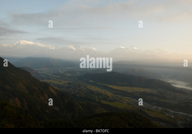 Mist rises over mountains at sunrise near Pokhara, Nepal on Tuesday October 27, 2009. - Stock Image