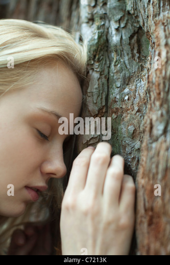Young woman leaning forhead against tree trunk, eyes closed - Stock-Bilder